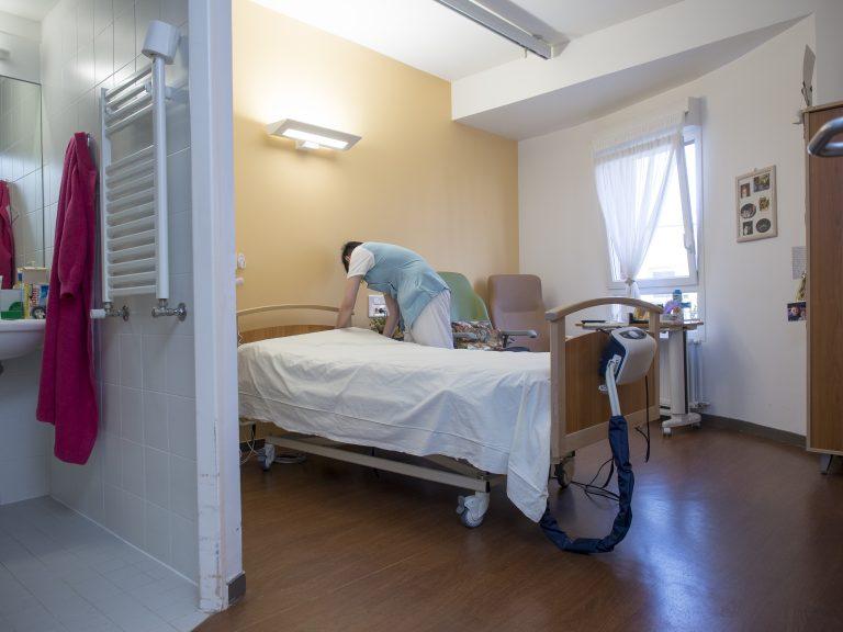 EHPAD, Les Jardins du Crinchon de Achicourt (Pas de Calais), Groupe AHNAC. Aide soignante faisant le lit dans une chambre.